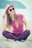 Счастливый турист женщины в соломенной шляпе и солнечных очках сидя на пляже, свободном времени на концепции взморья Стоковые Фотографии RF