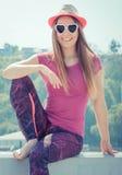 Счастливый турист женщины в соломенной шляпе и солнечных очках сидя на пляже, свободном времени на концепции взморья Стоковая Фотография