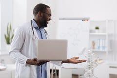 Счастливый умный доктор указывая на модель дна Стоковые Фотографии RF
