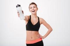 Счастливый усмехаться резвится женщина передавая бутылку с водой к камере Стоковое Изображение RF