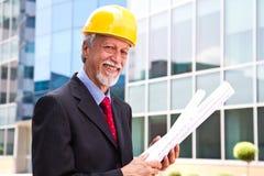 Счастливый, усмехаясь более старый архитектор смотря вне стоковые фото