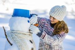 Счастливый усмехаясь девочка-подросток играя с снеговиком Стоковое Изображение RF