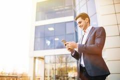 Счастливый усмехаясь костюм бизнесмена нося и использование современного smartphone около офиса на рано утром Стоковые Фотографии RF