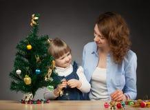 Счастливый усмехаясь ребёнок и ее мумия украшают рождественскую елку Стоковые Изображения RF