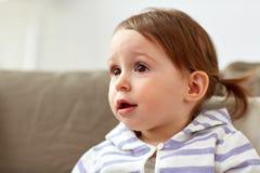 Счастливый усмехаясь ребёнок сидя на софе дома Стоковые Фото