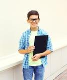 Счастливый усмехаясь умный мальчик подростка в стеклах с папкой или книгой Стоковое фото RF