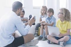 Счастливый учитель показывает детям робот стоковая фотография