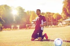 Счастливый футболист с шариком на футбольном поле стоковая фотография