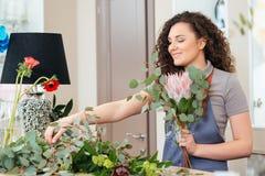 Счастливый флорист женщины делая букет на таблице в магазине Стоковое Фото