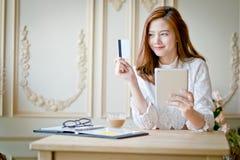 Счастливый ходить по магазинам женщины онлайн, держащ кредитную карточку, используя таблетку c Стоковое Фото