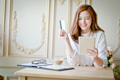 Счастливый ходить по магазинам женщины онлайн, держащ кредитную карточку, используя таблетку c Стоковые Изображения RF
