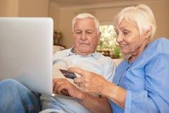 Счастливый ходить по магазинам старшиев онлайн с кредитной карточкой от дома Стоковая Фотография