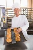 Счастливый хлебопек держа поднос свежего хлеба Стоковое фото RF