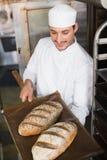 Счастливый хлебопек держа поднос свежего хлеба Стоковое Фото