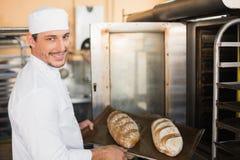 Счастливый хлебопек держа поднос свежего хлеба Стоковые Фотографии RF