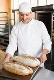 Счастливый хлебопек держа поднос свежего хлеба Стоковая Фотография
