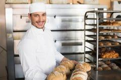 Счастливый хлебопек показывая поднос свежего хлеба Стоковые Изображения RF