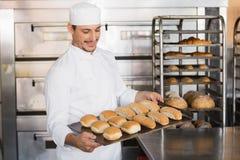 Счастливый хлебопек показывая поднос свежего хлеба Стоковое Изображение