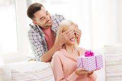 Счастливый человек давая подарочную коробку женщины дома Стоковая Фотография RF