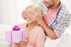 Счастливый человек давая подарочную коробку женщины дома Стоковые Фотографии RF