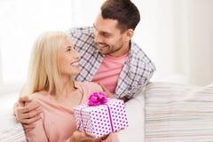 Счастливый человек давая подарочную коробку женщины дома Стоковые Изображения RF