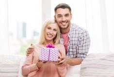 Счастливый человек давая подарочную коробку женщины дома Стоковые Фото
