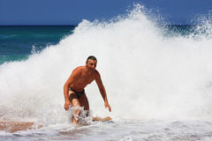Счастливый человек будучи брызганным волной на пляже Стоковое Изображение RF