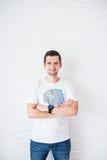 Счастливый человек в белой футболке и голубых джинсах на белой предпосылке смотря камеру Стоковая Фотография RF