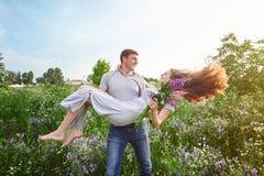 Счастливый человек влюбленности держа женщину на его оружиях в поле Стоковые Изображения