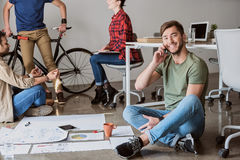 Счастливый человек говоря на smartphone в офисе Стоковое Изображение RF
