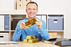 Счастливый человек держа золото в слитках в офисе стоковая фотография rf