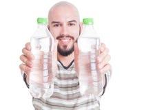 Счастливый человек держа 2 пластичных бутылки воды Стоковые Фото