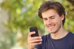 Счастливый человек используя умный телефон внешний стоковое изображение