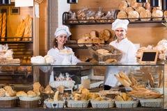 Счастливый человек и девушка продавая печенье и хлебцы стоковое фото rf