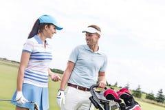 Счастливый человек и женщина беседуя на поле для гольфа против ясного неба Стоковое Фото