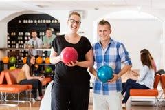 Счастливый человек и женщина держа шарики боулинга в клубе Стоковые Фото