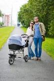 Счастливый человек и женщина идя с pram младенца Стоковая Фотография