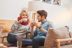 Счастливый человек и женщина наслаждаясь горячим питьем Стоковые Изображения RF