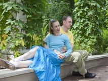 Счастливый человек и женщина сидят на стенде в парке в лете Стоковое фото RF