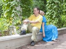 Счастливый человек и женщина сидят на стенде в парке в лете Стоковое Изображение RF