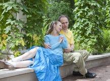 Счастливый человек и женщина сидят на стенде в парке в лете Стоковые Изображения RF