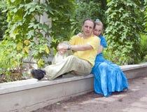 Счастливый человек и женщина сидят на стенде в парке в лете Стоковое Изображение