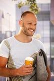 Счастливый человек идя на улицу держа кофе Стоковая Фотография RF