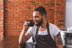 Счастливый человек наслаждаясь latte в кофейне стоковое изображение rf