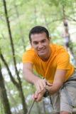 Счастливый человек на весьма парке веревочки с carabiners Стоковое Фото