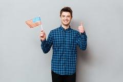 Счастливый человек показывая большие пальцы руки вверх и держа флаг США стоковое изображение rf