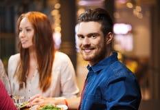 Счастливый человек при друзья имея обедающий на ресторане Стоковые Фотографии RF