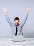 Счастливый человек работая на компьтер-книжке в офисе Стоковая Фотография