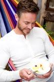 Счастливый человек сидя в гамаке есть фруктовый салат Стоковое фото RF