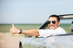 Счастливый человек управляя автомобилем и показывая большие пальцы руки вверх стоковые изображения rf